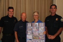 """Mary presents """"Thank You"""" Poster to Engineer Neil Wagner, Captain Doug Chalmers and Paramedic Matt Drabinski"""